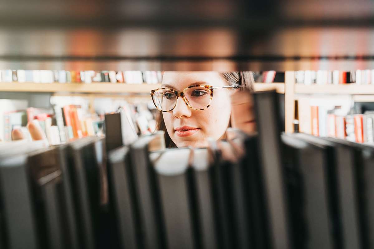 A women looking through a bookshelf