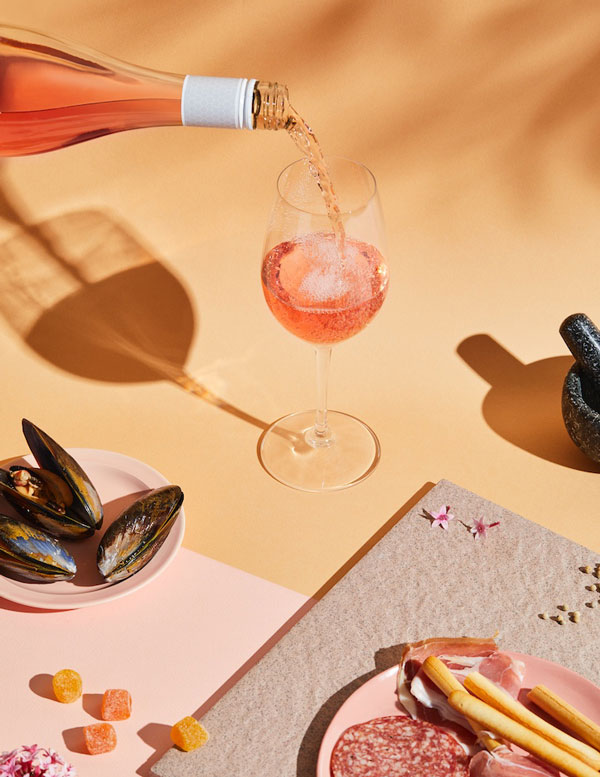 Product photography by the Brand Good Pair Days. A glass of rose wine is being poured. There's a pale orange background and plates of oysters and antipasto. There are deep shadows from the products.