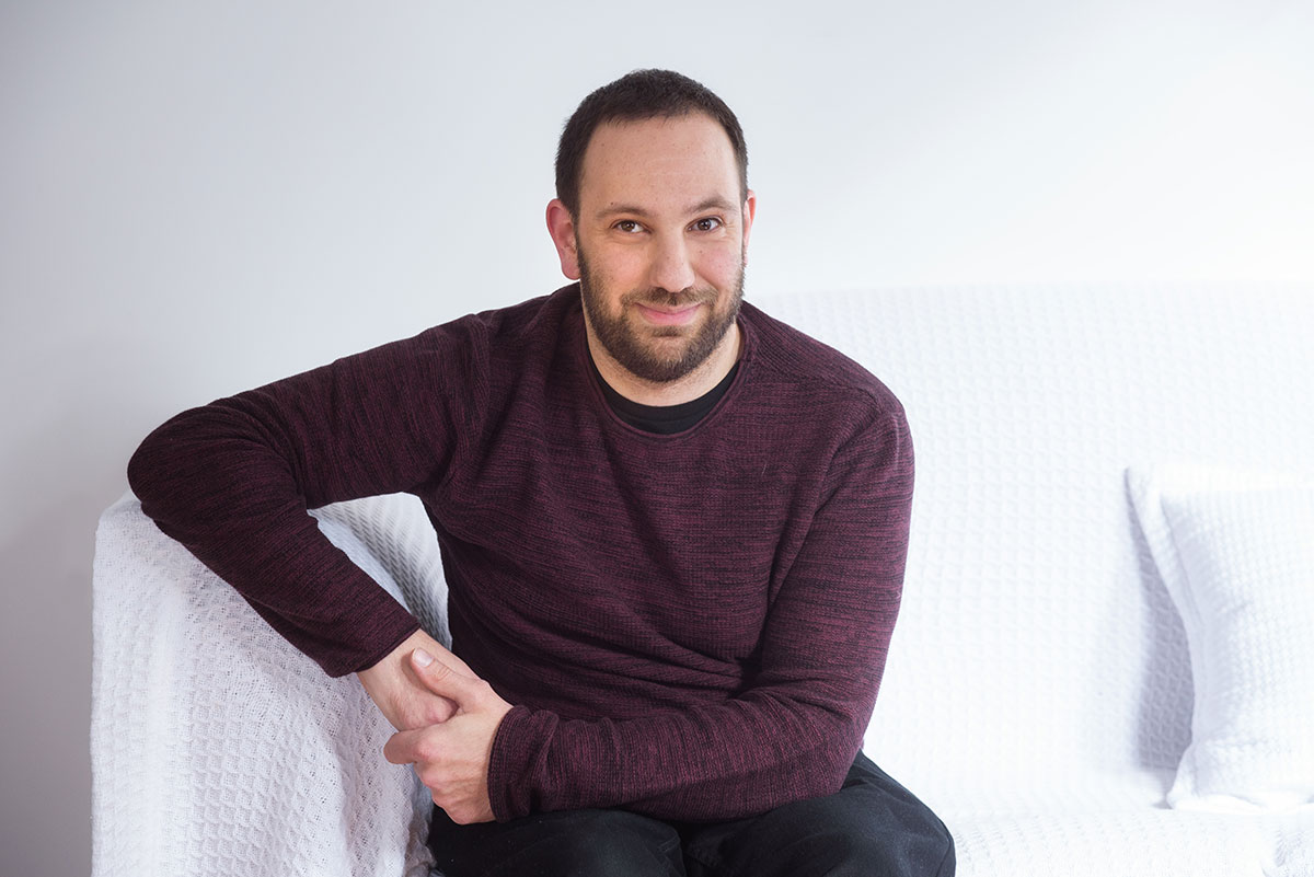 Digital accessibility expert Adem Cifcioglu is sitting on a white couch and looking at the camera.