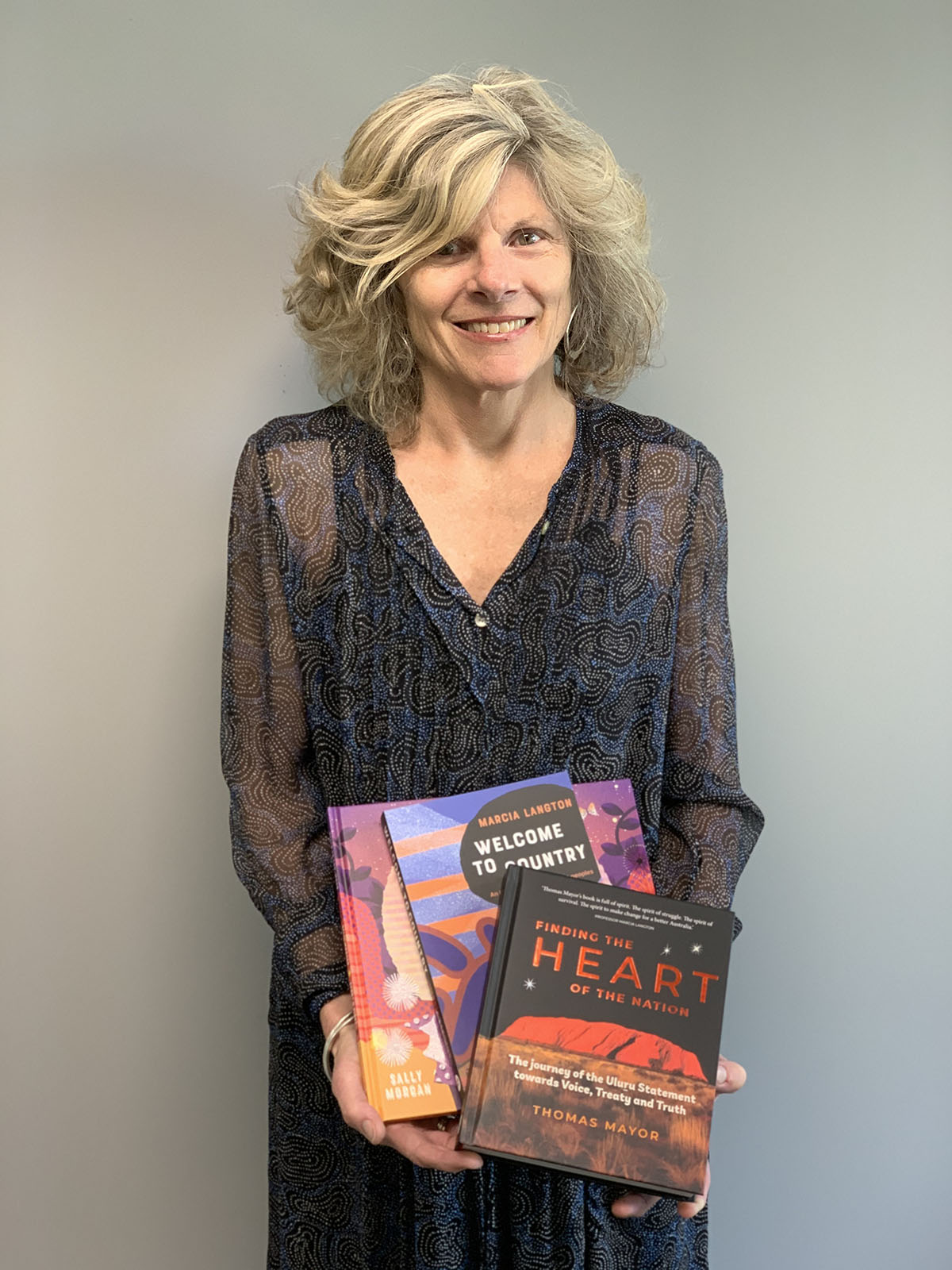 Fiona Hardie holding some of Hardie Grant's Aboriginal and Torres Strait Islander authored books