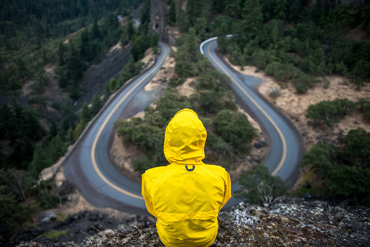 A person wearing a yellow raincoat sits with their back to the camera. They are looking at a winding road.