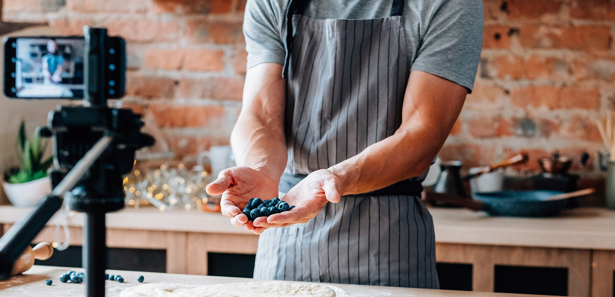 A chef holding berries in front of a phone that is filming him