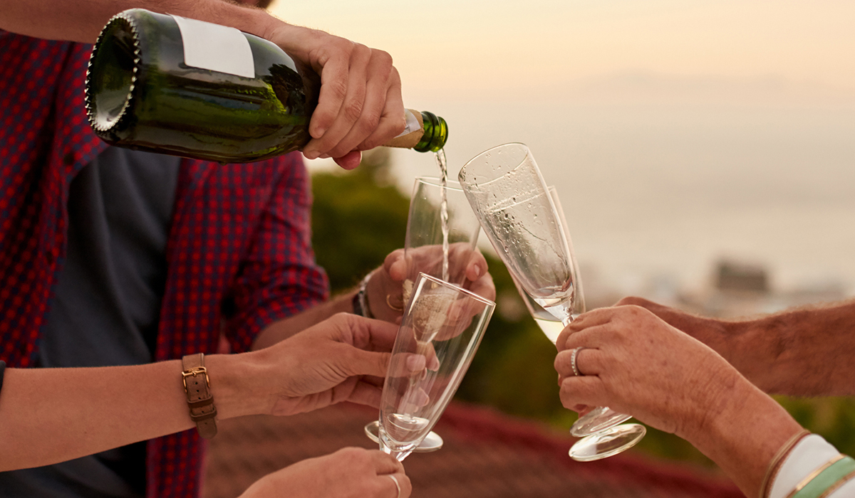 Four outstretched hands holding flutes and one person pouring sparkling wine