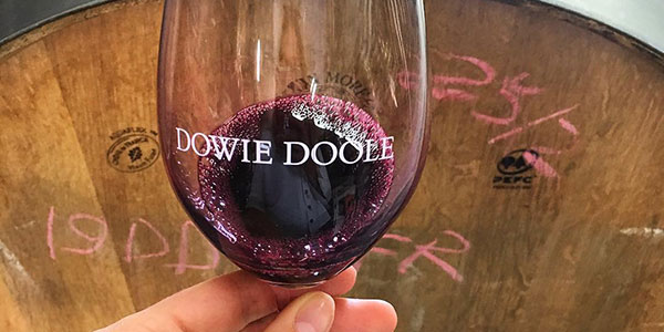 Dowie Doole red wine in glass with barrel in the background