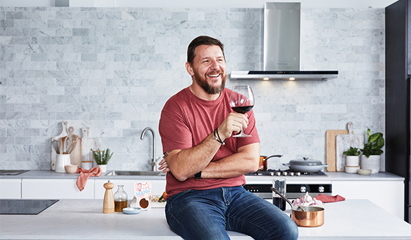 Chef Manu Feildel with a glass of wine