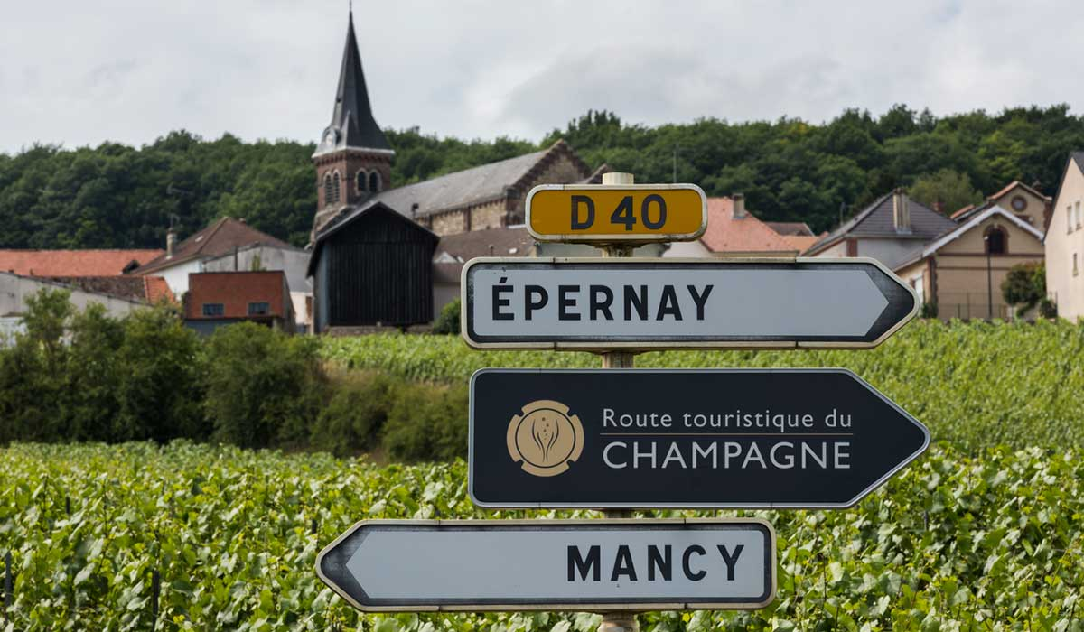 Sign of the tourist route in Champagne with vineyards and a village in the background.