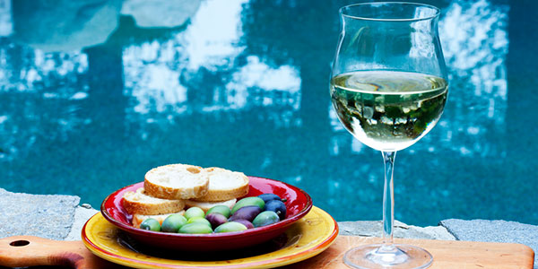 Glass of wine and bowl of olives by pool