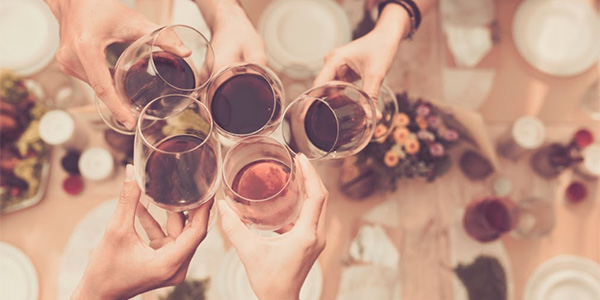 Friends clinking red wine glasses over table