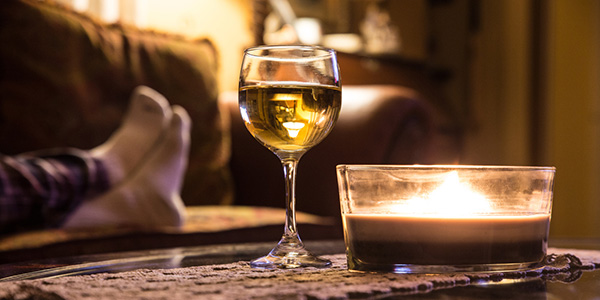 Glass of wine on coffee table with person on couch in the background