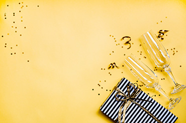 Festive yellow background with Champagne flutes, a present and confetti