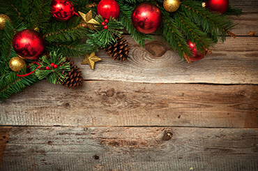 Christmas baubles, tree and pine cones against wooden background