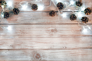 Pine cones and white festive lights against wooden background