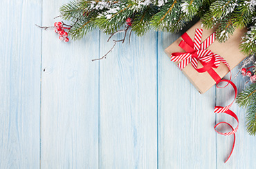Present and Christmas tree leaves against blue wooden background