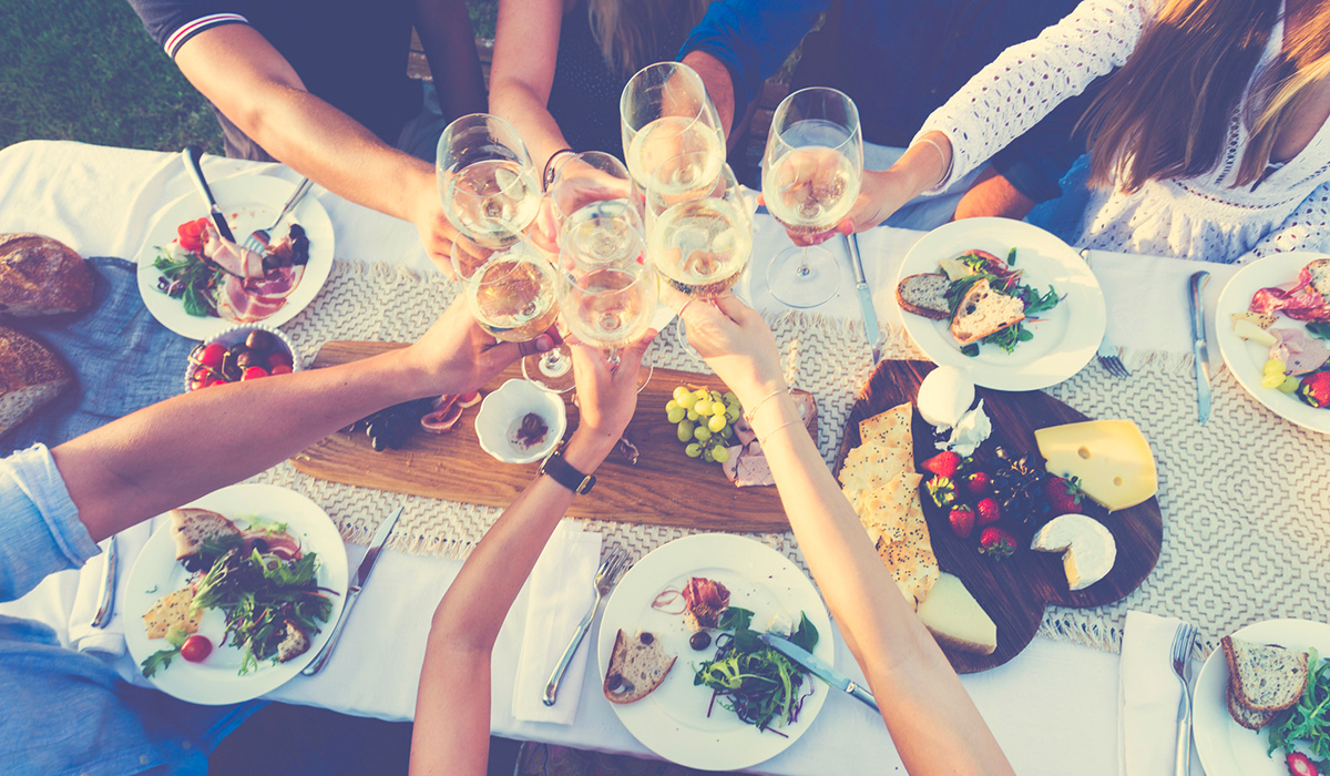 A group of people cheers with glasses of white wine over a table with food on plates, aerial view
