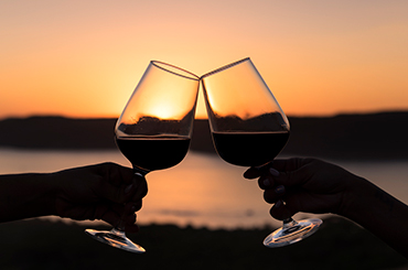 Two hands clinking glasses of red wine at sunset