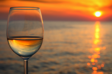 White wine by the water with sunset reflections