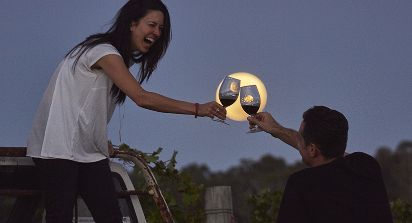 Two people celebrating with two glasses of Cullen wine under a full moon